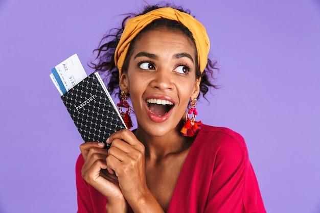 Игривая африканская женщина в платье держит паспорт с билетами, глядя на фиолетовую стену