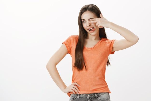 遊び心のある面白い美しい少女は片目を覆い、舌を見せて