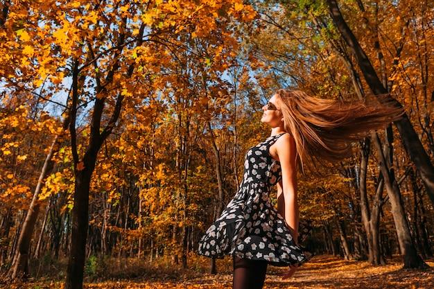 Шаловливая и счастливая девушка подростка с развевать заволакивает длинные волосы в прядении летать и танцевать в парке осени на солнечный день. прогулка по осеннему парку. свободная счастливая женщина. пространство для копирования.