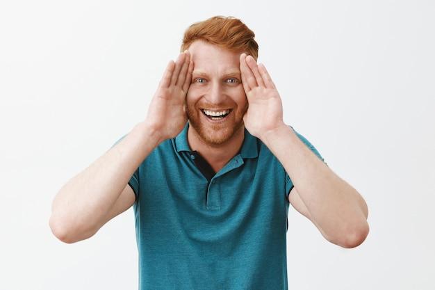 顔に沿って手のひらを保持し、広く笑って、ピーカブーを再生する剛毛を持つ遊び心のある、楽しいハンサムな若い赤毛の男