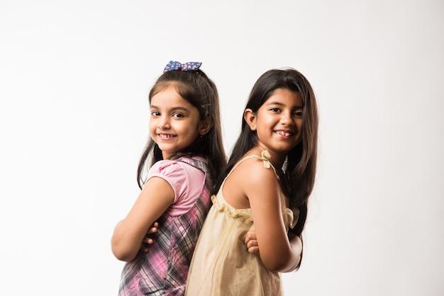 장난기 많고 예쁜 인도 또는 아시아의 작은 자매나 친구들이 장난기 가득한 분위기에서 포옹하고 춤을 추고 서로를 밀어줍니다. 흰색 배경 위에 절연