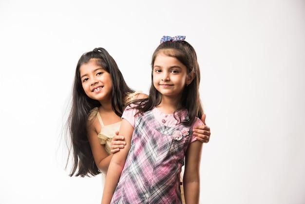 遊び心のある、かわいいインド人またはアジア人の妹や友達が遊び心のある気分で、抱き合ったり、踊ったり、お互いを押し合ったりします。白い背景の上に分離