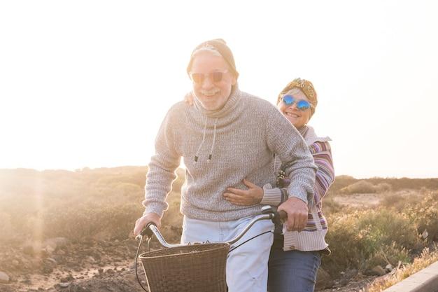 장난스럽고 젊은 수석 백인 부부는 함께 웃고 웃고 자전거를 타고 즐길 수 있습니다.