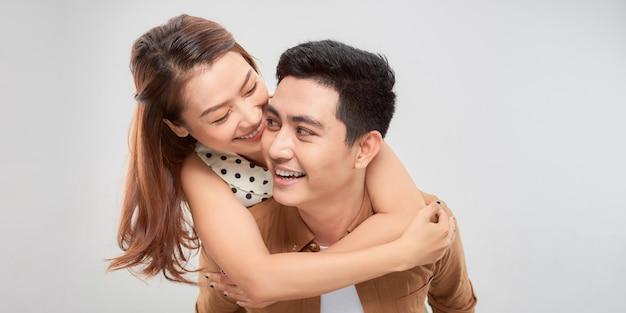 Игривый азиатский счастливый человек, совмещающий симпатичную женщину на простом белом фоне