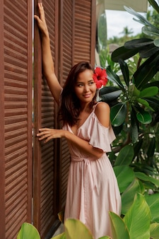 髪とピンクのドレスで豪華なトロピカルリゾートでポーズをとってハイビスカスの花と遊び心のあるアジアの女性。