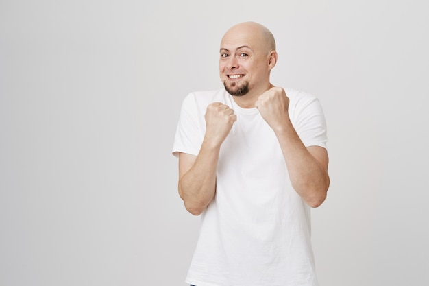 Playful bald guy clench fists, want fight