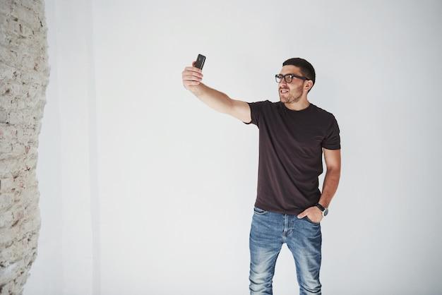Игривый бородатый мужчина делает селфи на смартфоне и белой стене