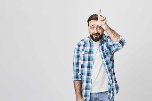 Playful bearded man showing loser sign, mocking