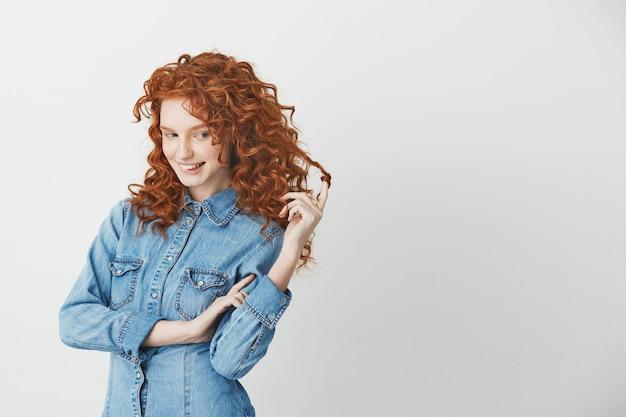 Игривая красивая девушка с рыжими волосами, думая, мечтая кусая губы.