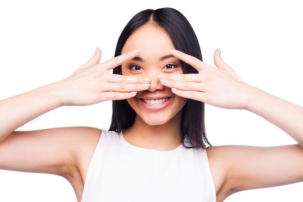 遊び心のある美しさ。カメラを見て、白い背景に立っている間彼女の顔を手で覆うかわいいドレスを着た美しい若いアジアの女性
