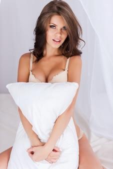Игривая красота. красивая молодая женщина с каштановыми волосами в нижнем белье, сидя в постели и обнимая подушку