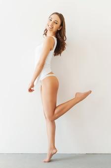 遊び心のある美しさ。白いタンクトップと白い背景に立ってポーズをとってパンティーの魅力的な若い女性の完全な長さ