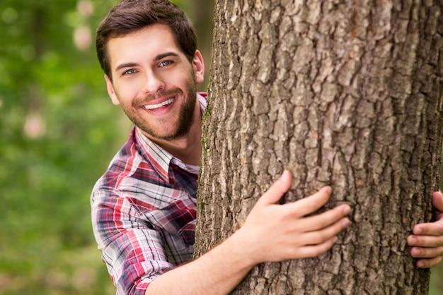 자연의 장난기 넘치는 아름다움. 나무 밖을 바라보며 웃고 있는 잘생긴 젊은 여성