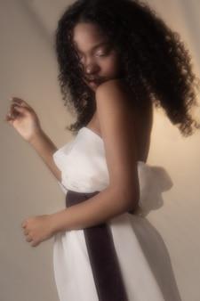 白いドレスでポーズをとる遊び心のある黒人の女の子。