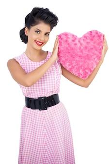 핑크 하트 모양의 베개를 들고 장난 검은 머리 모델