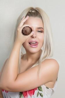 手にカップケーキを楽しんで、彼女の目を覆っている遊び心のあるブロンドの女の子。ベーカリーとお菓子のコンセプト。テキスト用のスペース