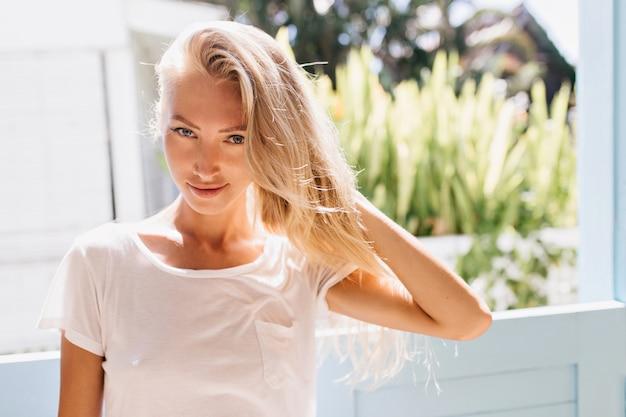 窓の近くでポーズをとる遊び心のあるブロンドの女の子。晴れた朝にリラックスしてトレンディな白いtシャツを着た美しいヨーロッパの女性。