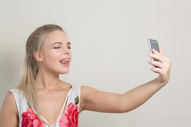 彼女の舌を見せて、携帯電話で自分撮りをする遊び心のあるブロンドの女性