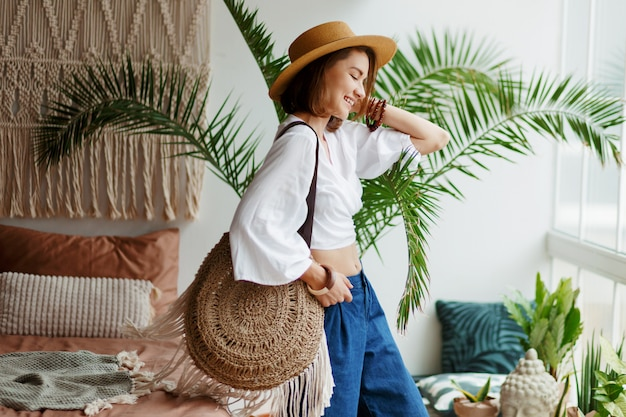 Playful bohemian woman posing in stylish bedroom with amazing interior, palms and macrame