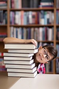 Playful boy hiding behind stack of books