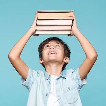 Playful boy holding stack of books