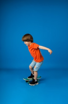 Playful boy with brown hair rides a skateboard on a blue surface with a place for text