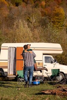 レトロなキャンピングカーの前でガールフレンドを空中で回転させる遊び心のあるボーイフレンド。