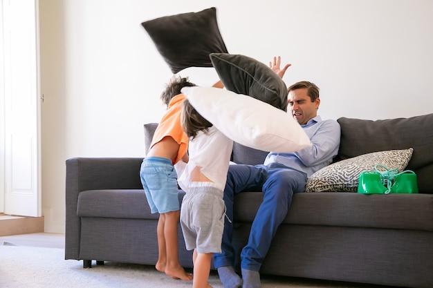 Игривые мальчики атакуют кавказского мужчину подушками. веселые дети играют и веселятся с отцом. папа закрывает глаза и защищается от нападения. концепция детства, семьи и игровой деятельности