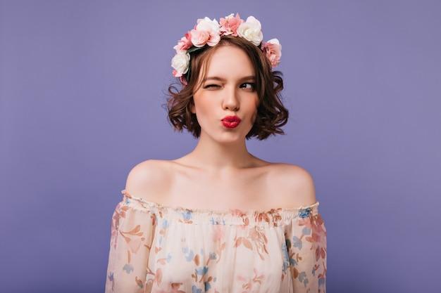 서 꽃의 고리에서 장난 갈색 머리 소녀입니다. 물결 모양의 머리가 귀여운 드레스를 입고 포즈를 취하는 jocund 여자의 실내 샷.