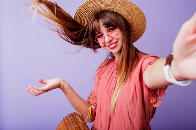 Donna castana allegra in cappello di paglia e occhiali da sole rosa che fanno autoritratto sopra il velluto. indossa un abito elegante.