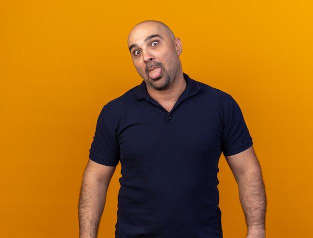 오렌지 벽에 고립 된 혀를 보여주는 장난 캐주얼 중년 남자