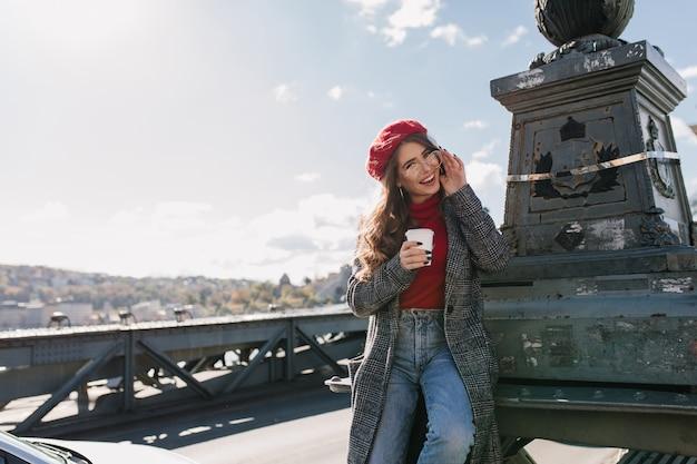 Игривая кавказская женщина в джинсах пьет кофе, исследуя европейский город