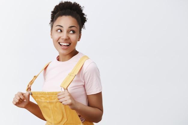 黄色いダンガリーの遊び心のある魅力的なフレンドリーなアフリカ系アメリカ人の女性、指でオーバーオールのストラップを伸ばし、広い笑顔で右を見つめ、灰色の壁を楽しんでいます