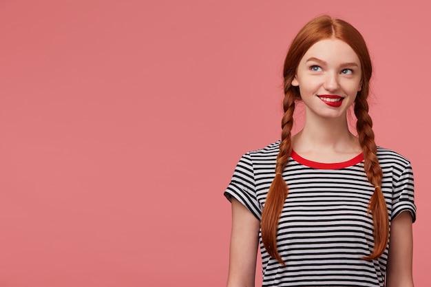 유혹 속에 빨간 입술을 물고있는 두 개의 빨간 머리 땋은 머리를 가진 장난기 가득한 매력적인 소녀, 벗겨진 티셔츠를 입고, 꿈꾸며 신중하게 복사 공간 옆에 서있는 왼쪽 상단을 바라 봅니다.