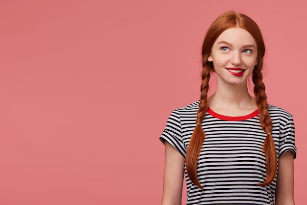 Giocosa e affascinante ragazza con due trecce dai capelli rossi che morde il labbro rosso all'interno della tentazione, vestita con una maglietta spogliata, guarda sognante pensierosa nell'angolo in alto a sinistra accanto allo spazio della copia