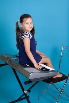 Playful child girl in a blue dress sits on synthesizer keys