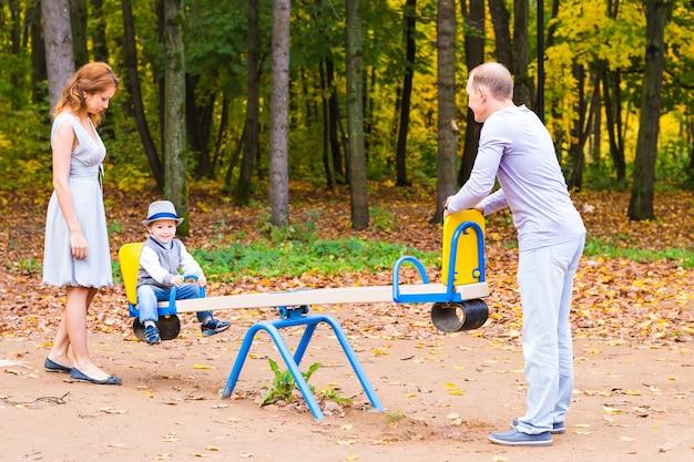 屋外の遊び場で両親と遊び心のある子供。ママ、パパ、子供