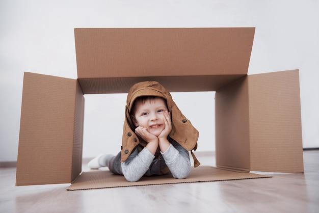 遊び心のある子供時代。段ボール箱を楽しんでいる少年。パイロットのふりをしている少年。家で楽しんでいる小さな男の子と女の子。