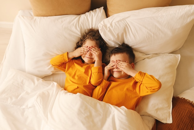 黄色のパジャマを着た遊び心のある子供たちは目を閉じてベッドに横になります
