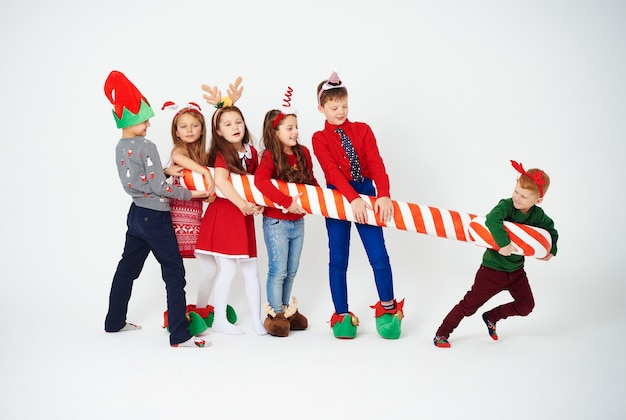 Playful children with big candy cane