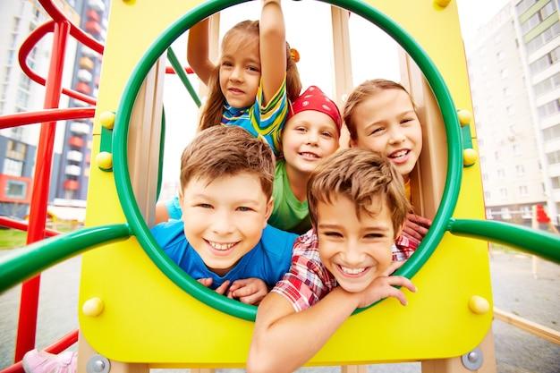 Игривые одноклассники с удовольствием на игровой площадке