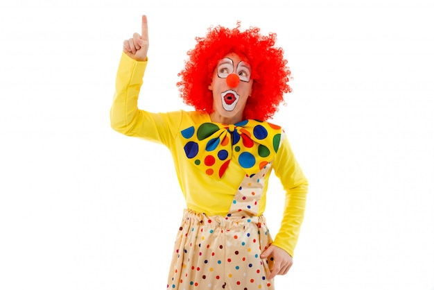 Playful clown in red wig pointing and looking upwards.