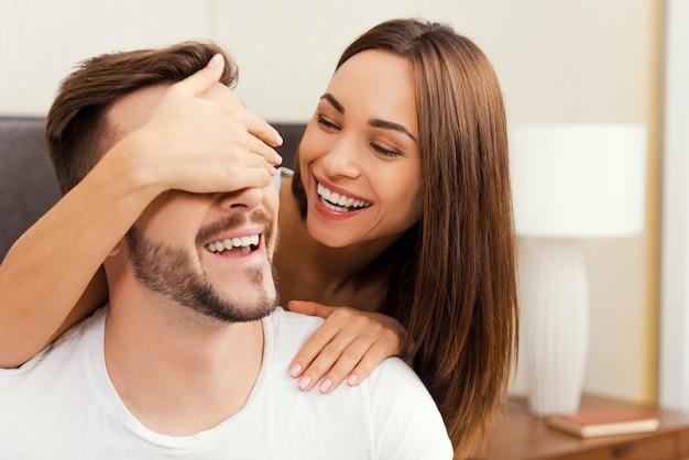 장난기 많은 커플. 함께 침대에 누워있는 동안 서로 결합하는 아름다운 젊은 사랑의 부부