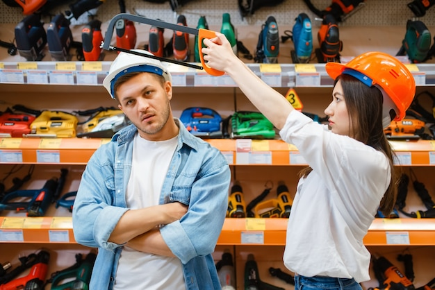 Playful couple choosing tools in hardware store.