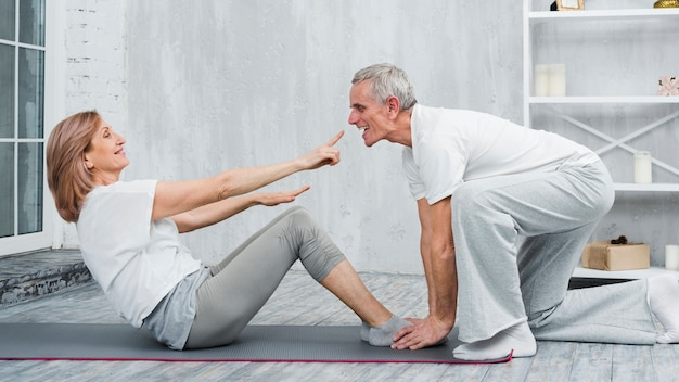 Playful couple doing yoga exercise at home