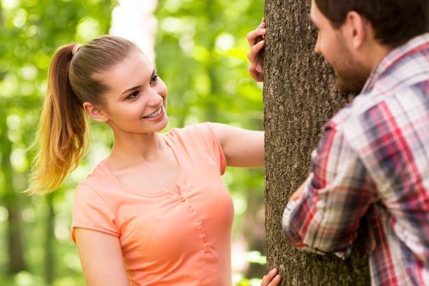 공원에서 장난 커플입니다. 나무 근처에 서 있는 동안 공원에서 재미 장난 젊은 부부