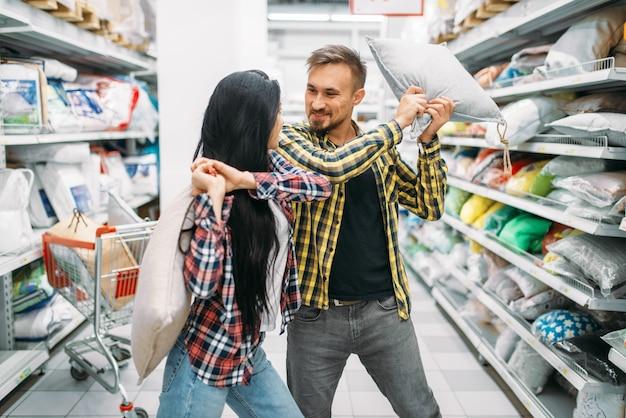 スーパーで遊び心のあるカップル、枕投げ