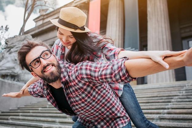 Игривая пара туристов снаружи на лестнице. бородатый молодой человек держит женщину на спине. они смотрят друг на друга и держат руки в стороне от тел.
