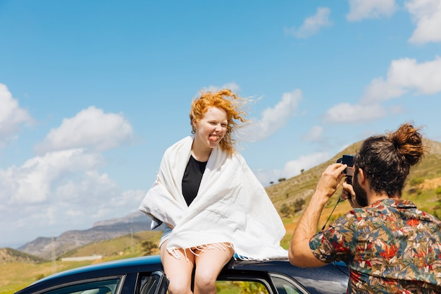 Playful couple taking photos on car roof
