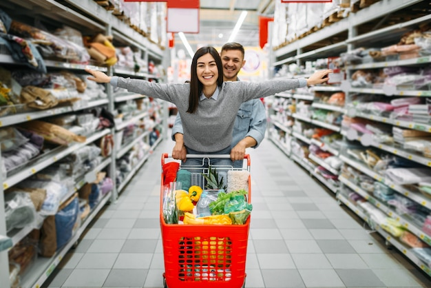 Playful couple with cart full of goods in store